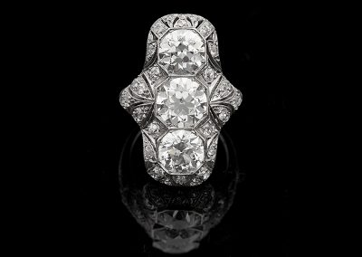 Old European cut diamond flanked by two 1.75 ct Old European cut diamonds and 1.25 carats of side diamonds in platinum
