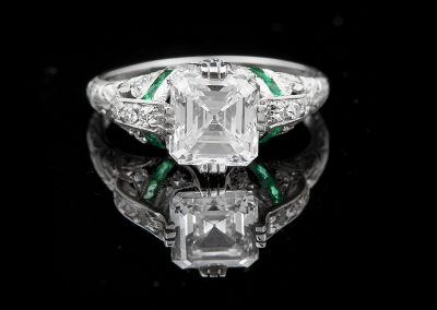 Estate ring with a 2.01 ct Asscher cut diamond and emeralds in platinum