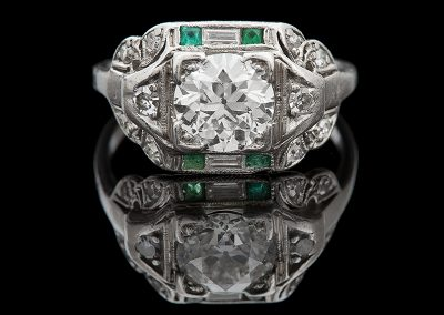 Art Deco ring with a 1.10 ct center diamond and side emeralds and diamonds in platinum