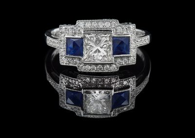 Ring with a 1 ct center diamond and 0.54 carats of sapphires with 0.24 carats of side diamonds in platinum