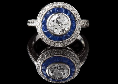 Ring with a 1 ct center diamond and side sapphires and diamonds in 18kt white gold