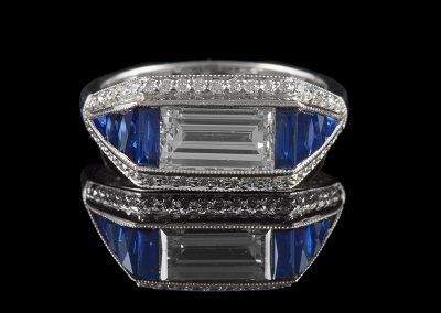 Ring with an emerald cut center diamond surrounded by sapphires and diamonds in platinum