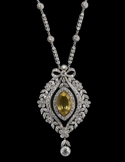 Estate yellow sapphire and diamond pendant brooch on a diamond and platinum chain