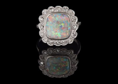 Art Deco ring with a cushion cut opal and 0.50 cts of diamonds in platinum