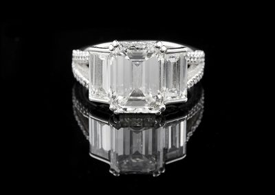 Ring with a 3.39 ct center emerald cut diamond and 1.80 carats of side diamonds in platinum